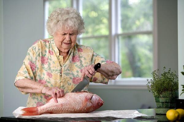 Elderly Woman Cutting Open a Fish