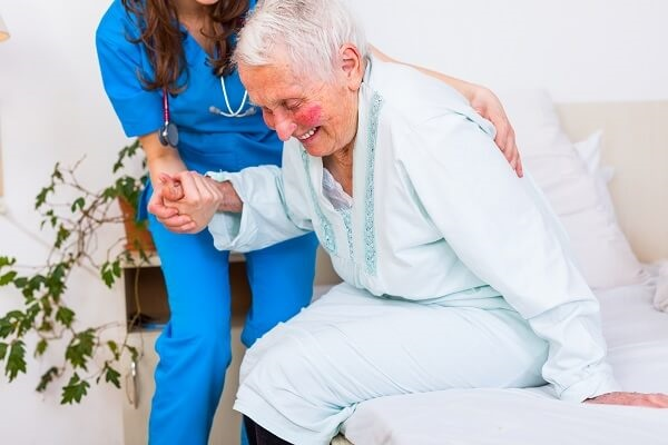 Nurse Helping Senior Get Out Of Bed
